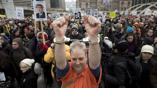 A demonstrator wears handcuffs while protesting on a national day of action against Bill C-51, the government's proposed anti-terrorism legislation, in Toronto on Saturday, March 14, 2015. THE CANADIAN PRESS/Darren Calabrese